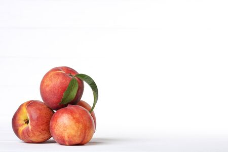 Fresh peaches with green leaf on white background 免版税图像