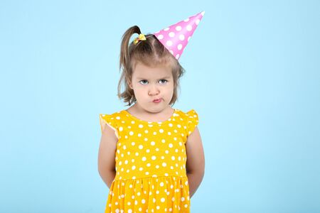 Cute little girl in birthday cap on blue background 스톡 콘텐츠