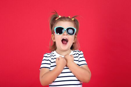 Cute little girl in sunglasses on red background