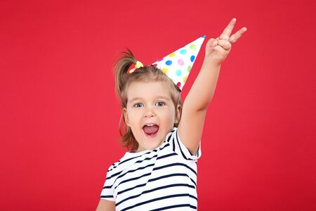 Cute little girl in birthday cap on red background