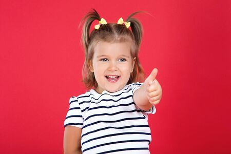 Cute little girl showing thumb up on red background