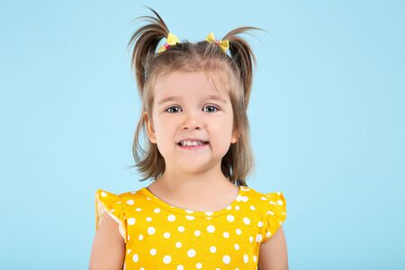 Cute little girl in yellow dress on blue background
