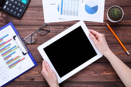 Tablet PC y papeles con gráficos y tablas sobre mesa de madera