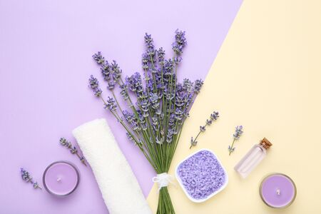 Lavender flowers with oil in bottle, candle and salt on colorful background