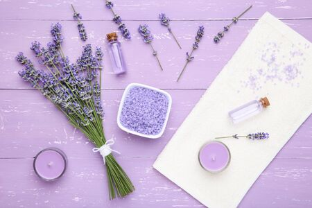 Lavender flowers with oil, salt and candle on puple wooden table