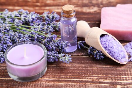 Lavender flowers with oil in bottle, candle and salt on brown wooden table