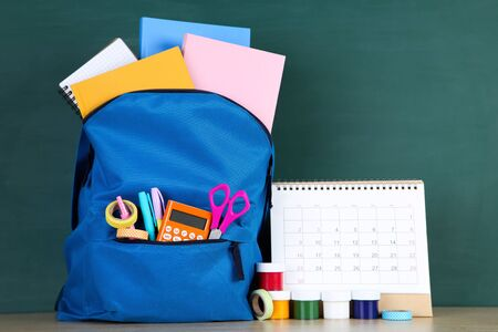 School supplies with blue backpack and paper calendar on blackboard background Imagens