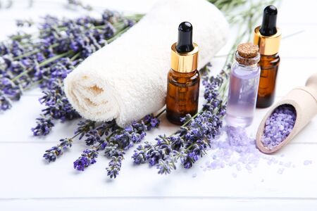 Lavender flowers with oil in bottles, salt and towel on white wooden table 写真素材