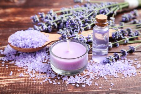 Lavender oil in bottle with flowers, salt and candle on brown wooden table 写真素材