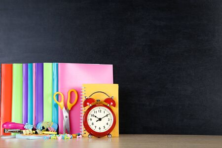 School supplies with red alarm clock on blackboard background