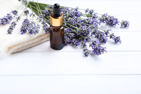 Lavender flowers with oil in bottle and towel on white wooden table