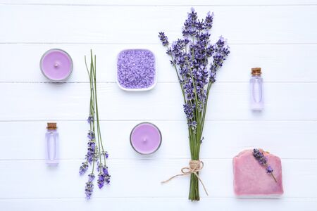 Lavender flowers with oil in bottles and soap on white wooden table