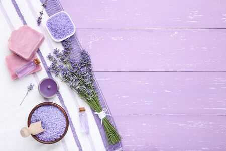 Lavender flowers with oil, soap and salt on puple wooden table 写真素材