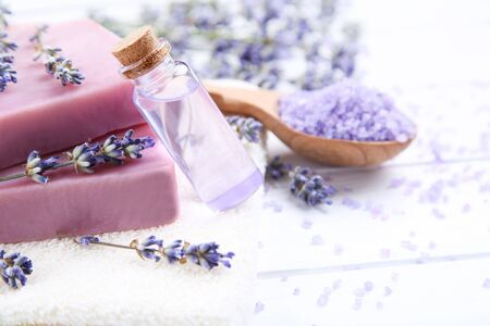 Lavender flowers with oil in bottle, soap and salt on white wooden table