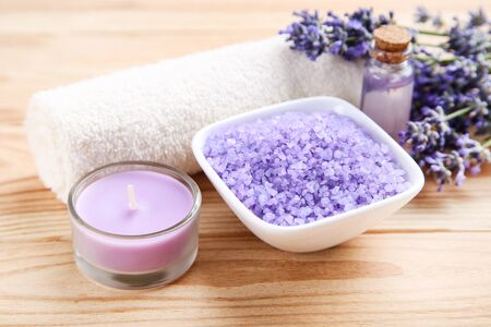 Lavender flowers with oil in bottle, salt in bowl and candle on brown wooden table 写真素材