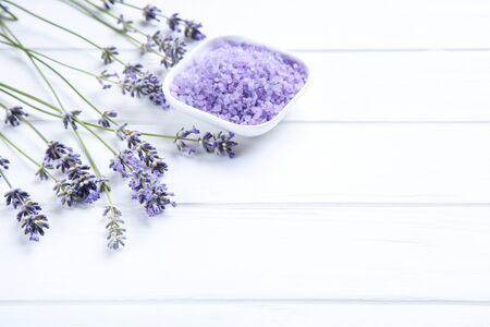 Lavender flowers and spa salt on white wooden table