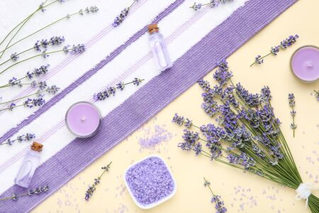 Lavender flowers with oil in bottles, salt and candle on beige background