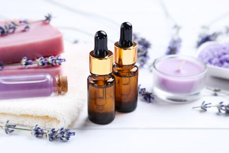 Lavender oil in bottles with flowers, candle and soap on white wooden table 写真素材