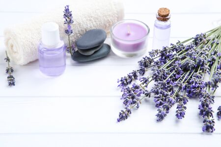 Lavender flowers with oil in bottles, candle and spa stones on white wooden table 写真素材