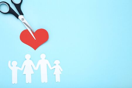 Family figures with scissors and red heart on blue background Stock Photo