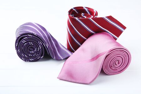 Colored neckties on white wooden table