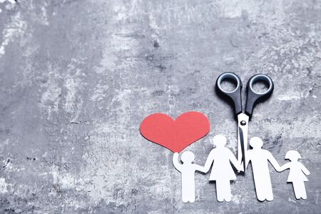 Family figures with red heart and scissors on grey background Stockfoto