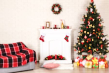 Blurred background of fireplace near sofa and christmas tree