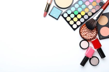 Makeup brush and different cosmetics on white background