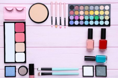 Different makeup cosmetics on pink wooden table