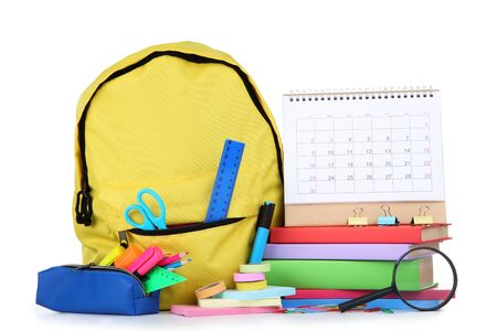 School supplies with yellow backpack and paper calendar on white background