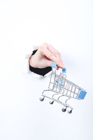 Hand holding shopping cart from white torn paper