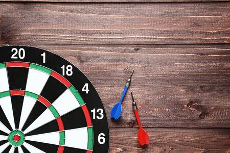 Dartboard with darts on brown wooden table Banco de Imagens - 128885090