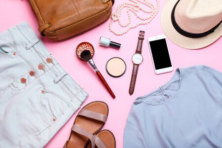 Modern women's clothes with accessories and makeup cosmetics on pink background