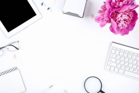 Tablet, keyboard computer with peony flower, glasses, notepad and earphones on white background Imagens - 128885128