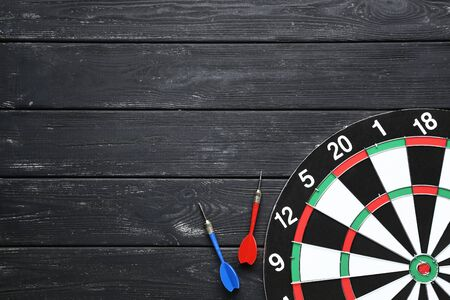 Dartboard with darts on black wooden table