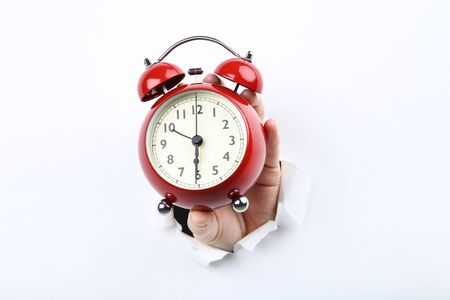Hand holding alarm clock from white torn paper