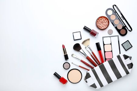 Makeup brushes and different cosmetics on white background Banco de Imagens