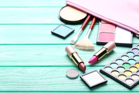 Different makeup cosmetics on mint wooden table Banco de Imagens