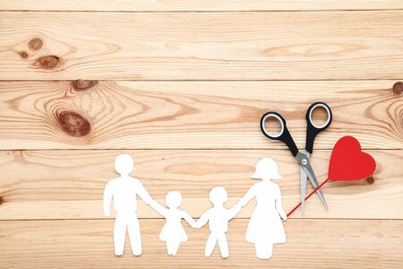 Family figures with scissors and red heart on wooden table