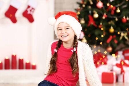Niña con sombrero de santa cerca del árbol de navidad en casa