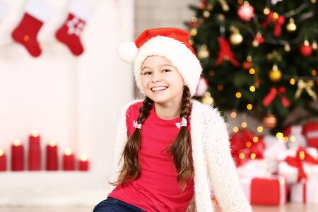 Young girl in santa hat near christmas tree at home