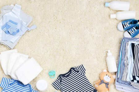Baby clothes with toys and diapers on carpet