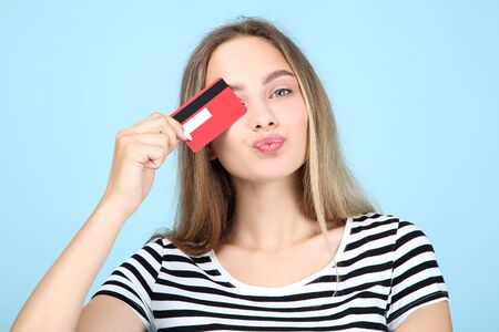Beautiful young woman holding credit card on blue background