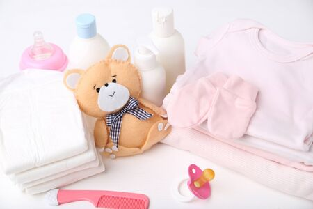 Folded clothes with diapers, baby supplies and soft bear toy 스톡 콘텐츠