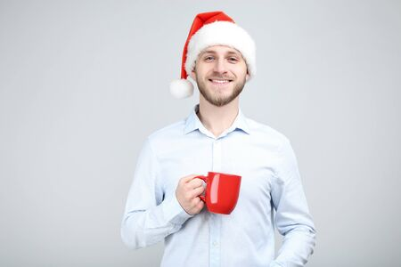 Portrait of young man with santa hat and red cup on grey background