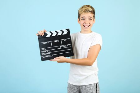 Young boy with clapper board on blue background Stockfoto