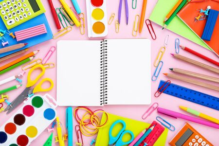 Different school supplies with opened notebook on pink