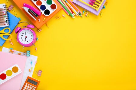 Different school supplies with alarm clock on yellow