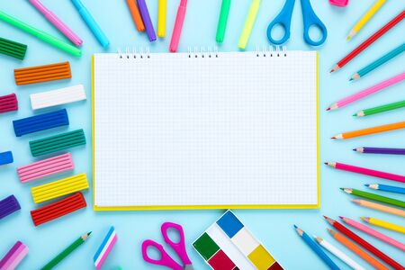 Different school supplies and blank sheet of paper on blue Stock fotó