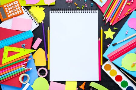 Different school supplies with blank sheet of paper on blackboard Stock fotó
